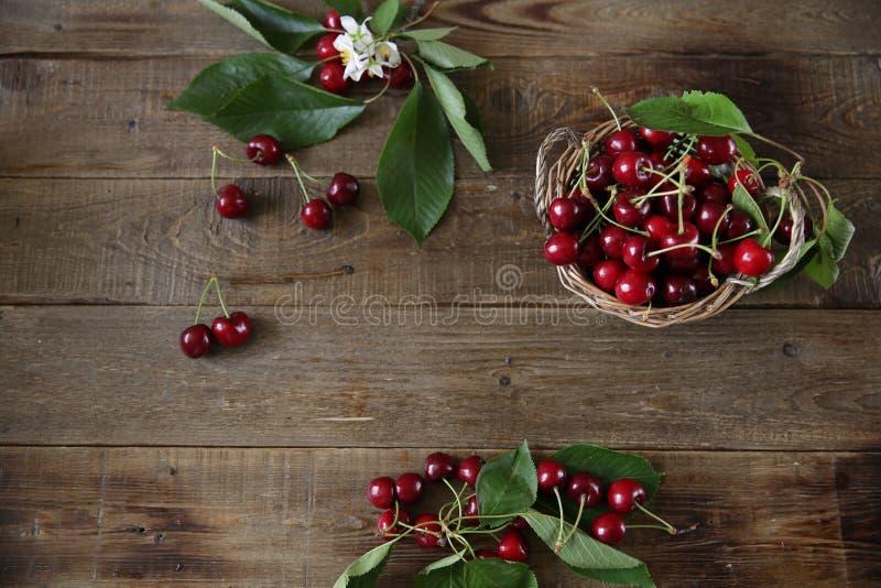 新鲜有机甜樱桃分支与的在木土气背景的绿色叶子 r r ? 免版税图库摄影