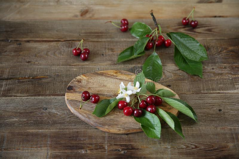 新鲜有机甜樱桃分支与的在木土气背景的绿色叶子 r r ? 库存照片