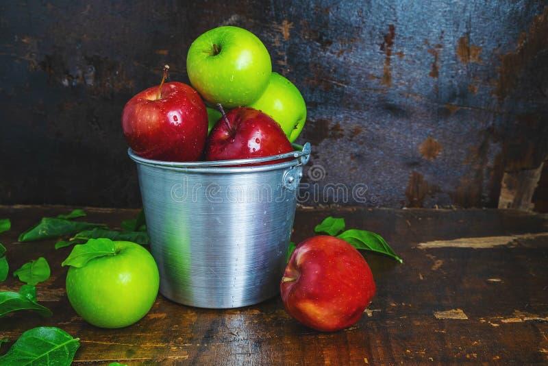 新鲜水果、绿色苹果和红色苹果在桶 免版税库存图片