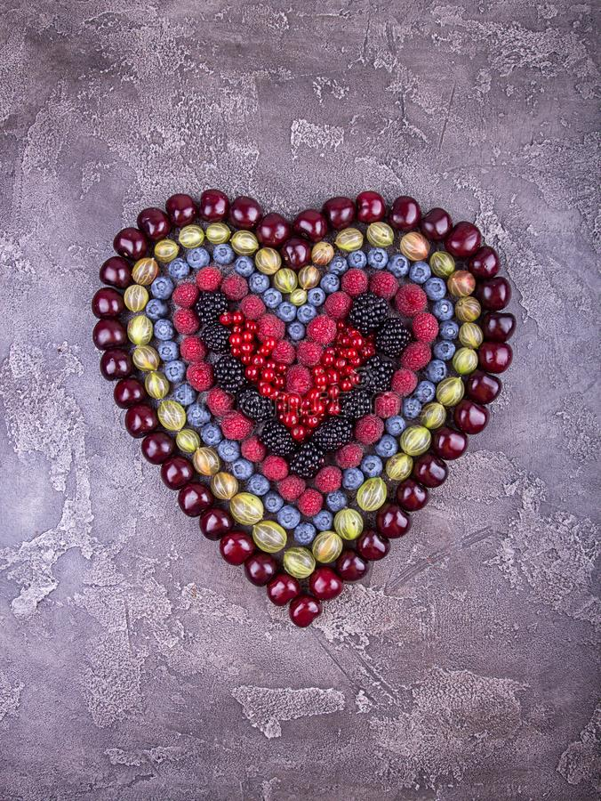 新鲜水果和莓果在心脏在具体灰色ba塑造  免版税库存图片