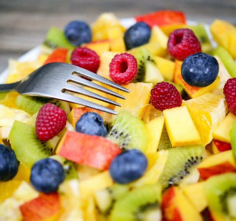 新鲜水果沙拉的宏观射击用香蕉猕猴桃橙色蓝莓和桃子与叉子 免版税库存照片