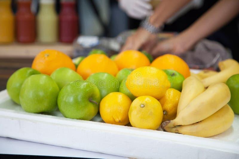 新鲜水果香蕉,桔子,石灰,在白色盘子的苹果品种在市场摊位,作为成份用于果子圆滑的人 库存照片