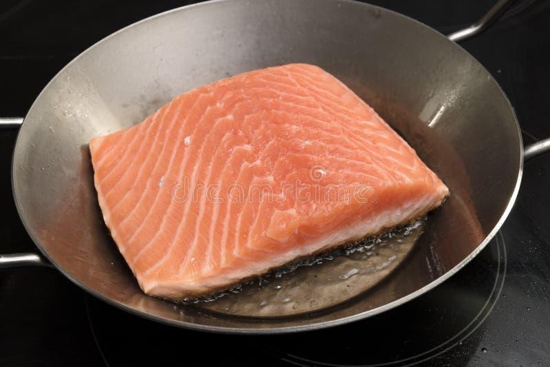 新鲜的三文鱼内圆角在火炉的铁平底锅油煎 图库摄影