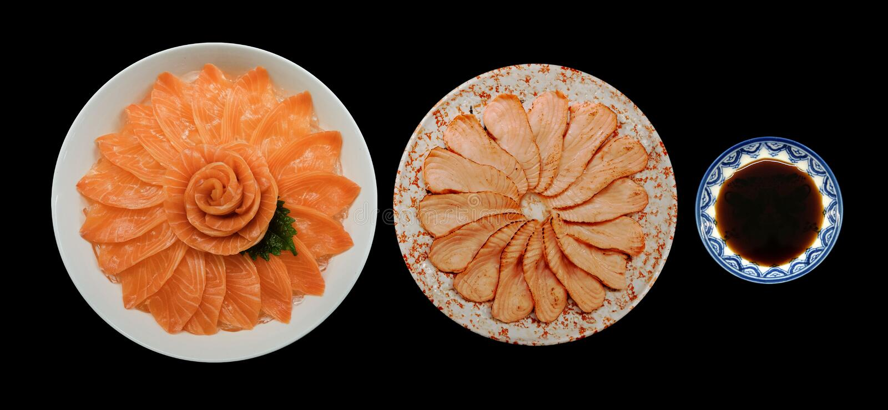 新鲜的三文鱼顶视图和格栅生鱼片和shoyu在黑背景隔绝的白色冰碗小船的花形状服务, Ja 库存照片