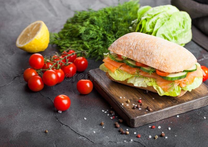 新鲜的健康三文鱼三明治用莴苣和黄瓜在葡萄酒砧板在黑石背景 早餐快餐 Fres 免版税库存照片