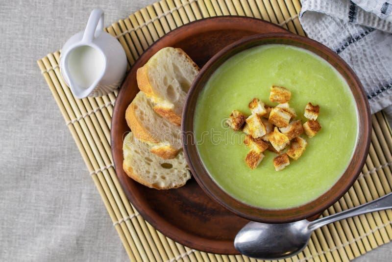 新鲜的健康奶油色汤用菠菜、奶油和油煎方型小面包片 免版税库存照片