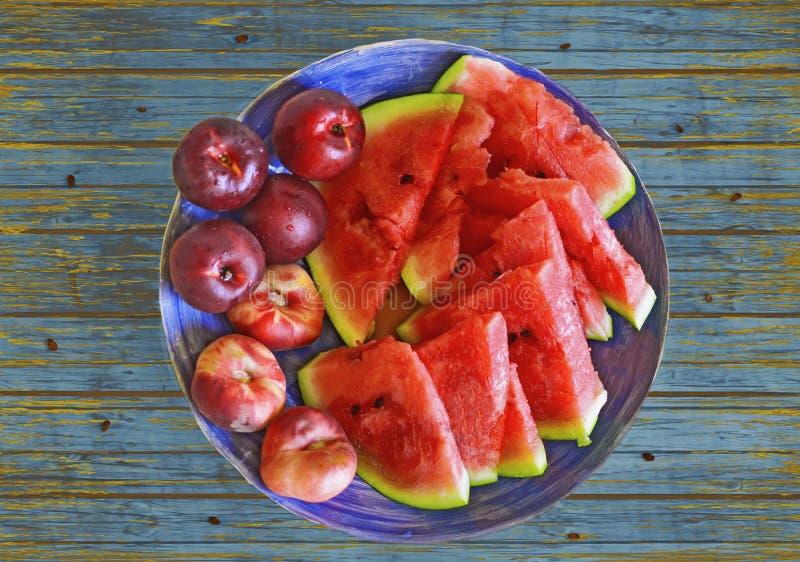 新鲜的健康果子:桃子、油桃和西瓜在葡萄酒木头纹理 免版税库存图片
