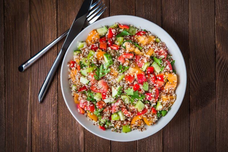 新鲜的健康沙拉用奎奴亚藜、五颜六色的蕃茄、甜椒、黄瓜和荷兰芹在木背景顶视图 免版税库存照片