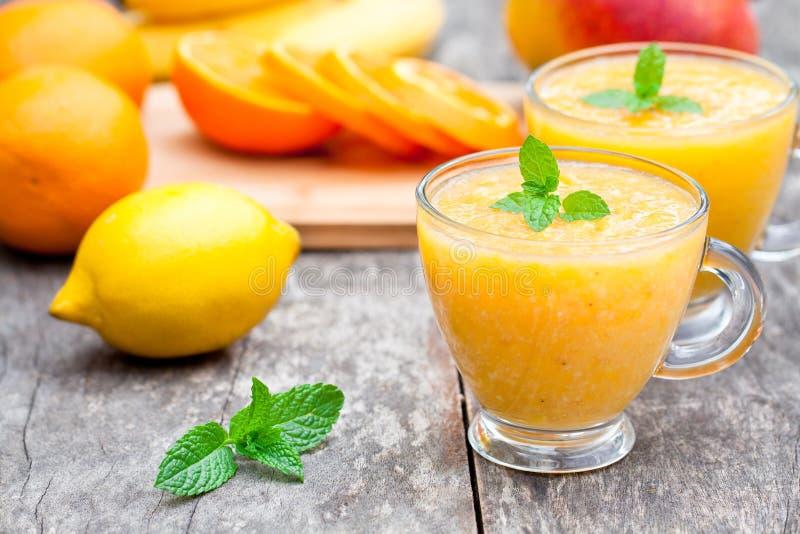 新鲜的健康稀烂汁液用橙色水果和蔬菜 免版税图库摄影