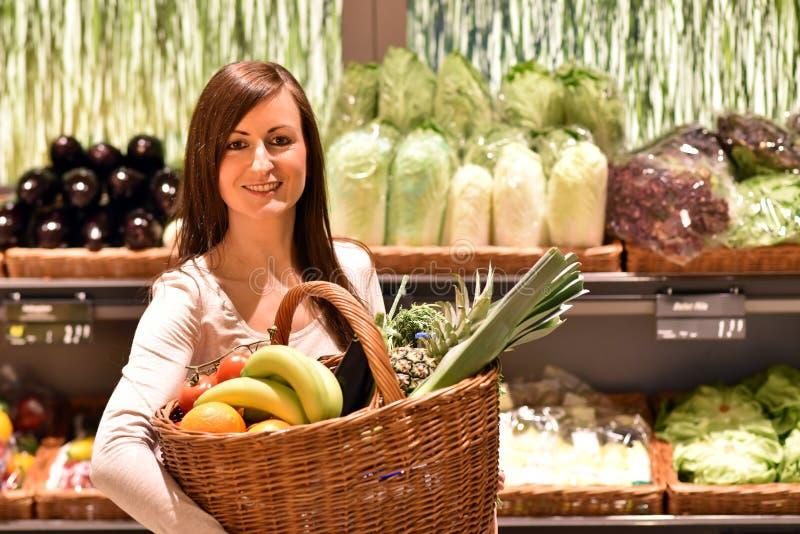 新鲜的健康食物的年轻俏丽的妇女购物在superm 库存图片