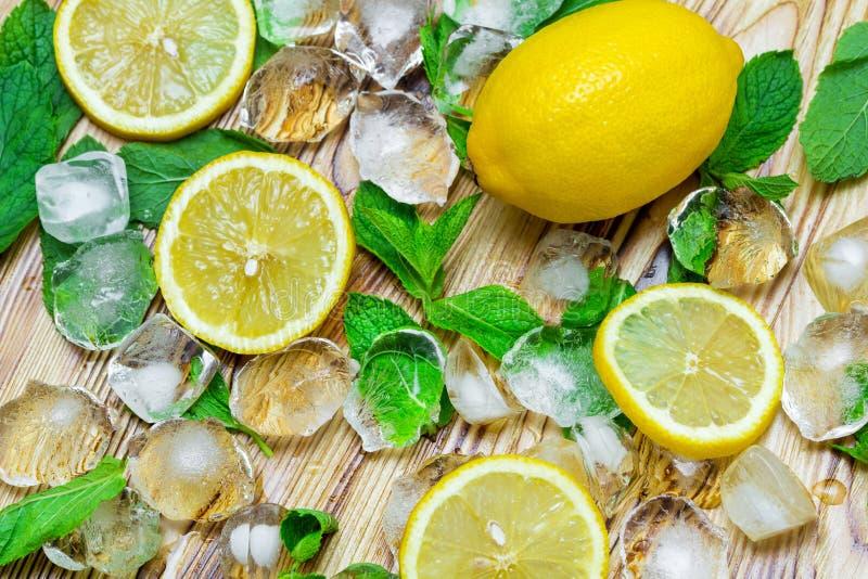新鲜的切的柠檬、鲜绿色的薄菏和冰在一张木桌上 一个非酒精Mojito鸡尾酒ingridients 库存照片