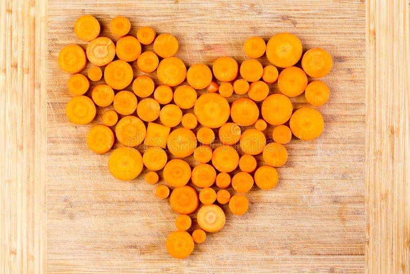 新鲜的切的橙色红萝卜在心脏安排了 库存图片