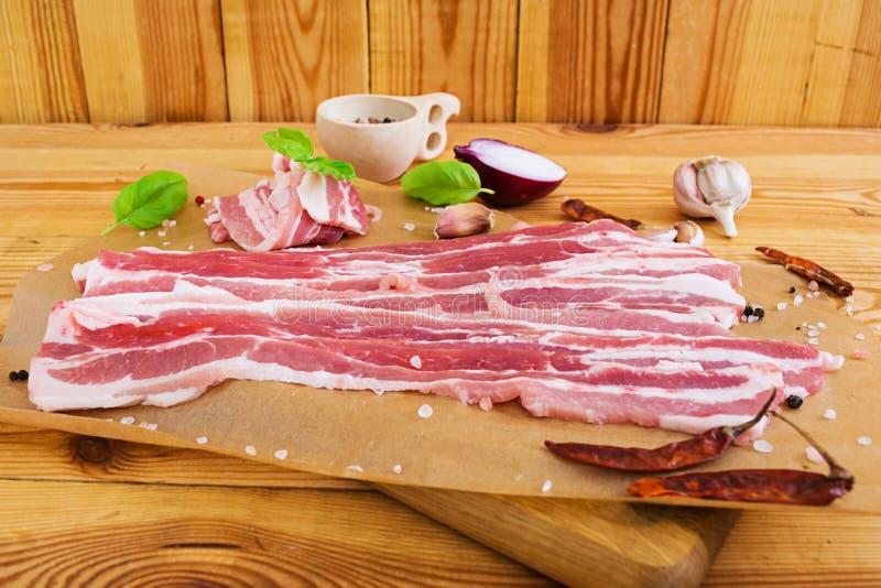 新鲜的切的烟肉用在白色背景的香料 免版税库存图片