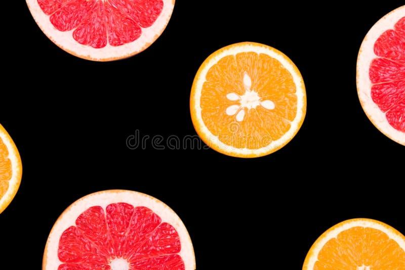 新鲜的半被切的在黑背景隔绝的葡萄柚和桔子 关闭视图 果子概念 概念健康生活方式 库存照片