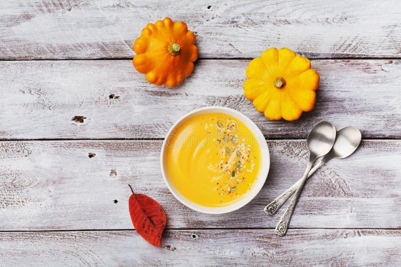 新鲜的南瓜汤装饰了种子和麝香草在白色碗在土气木台式视图 为秋天菜单射击的舒适生活方式 库存图片