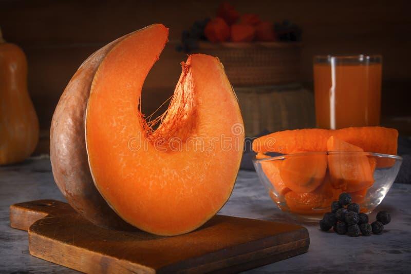 新鲜的南瓜片断在一个木板的以切好的红萝卜、一杯汁液和一个柳条筐为背景 免版税库存图片