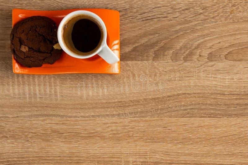 新鲜的咖啡和在板材安置的巧克力饼干,左上部角落 免版税库存照片