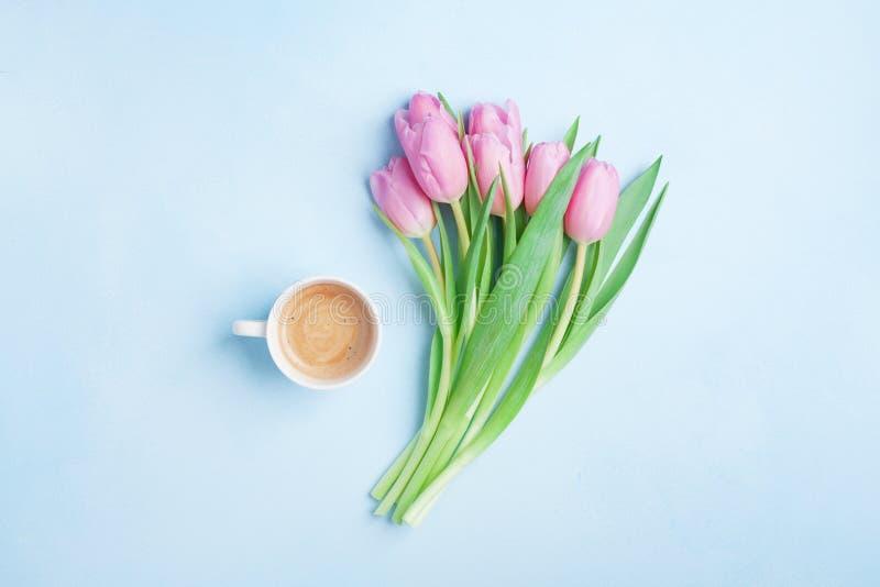 新鲜的咖啡和桃红色郁金香在淡色背景顶视图开花 美丽的春天早餐在母亲或妇女天 平的位置 图库摄影