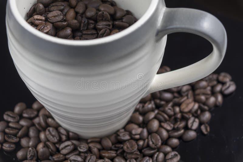 新鲜的咖啡豆关闭与杯子 免版税库存照片