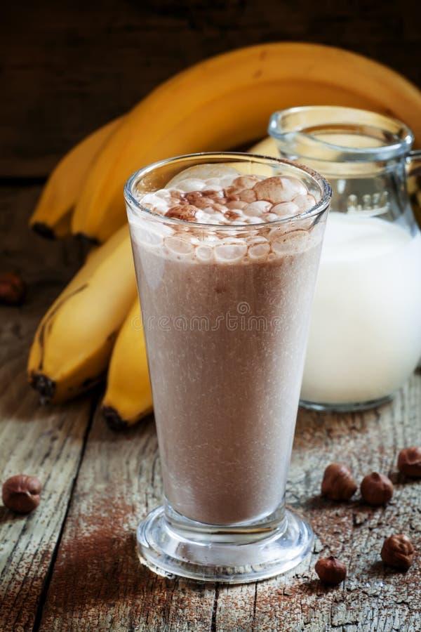 新鲜的圆滑的人香蕉和巧克力、牛奶和坚果在一大gl 免版税库存照片