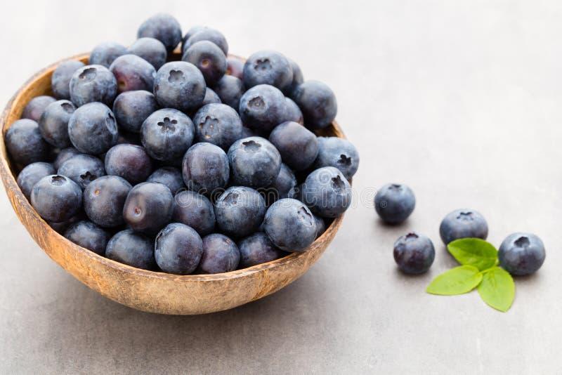 新鲜的在一个碗的蓝莓自然椰子在灰色背景 图库摄影