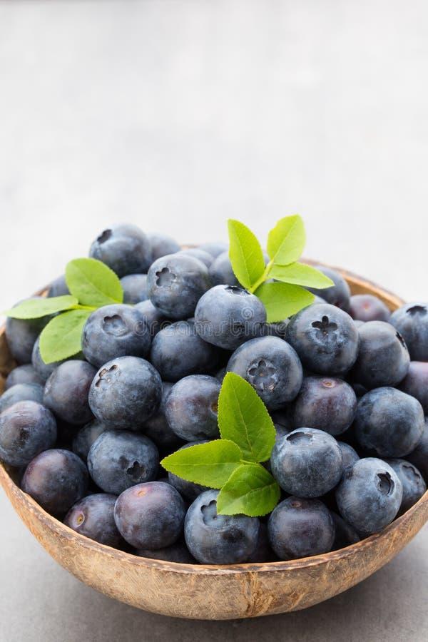 新鲜的在一个碗的蓝莓自然椰子在灰色背景 库存照片