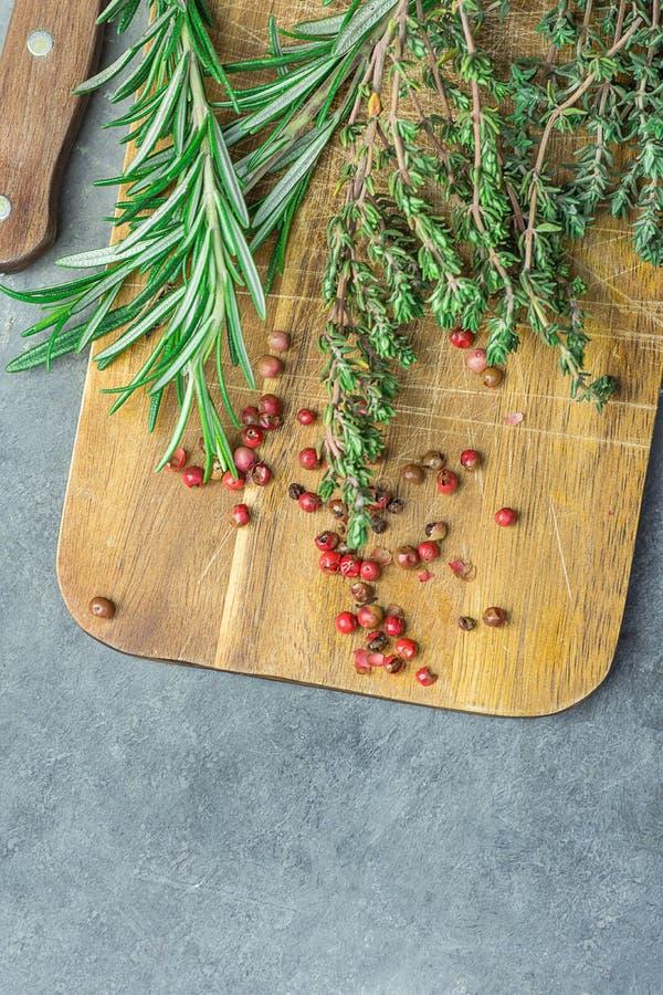 新鲜的在年迈的木切板刀子的普罗旺斯草本罗斯玛丽麝香草枝杈红色桃红色胡椒在黑暗的具体石表上 顶视图 免版税库存图片