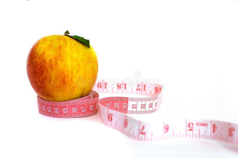 新鲜的在白色背景隔绝的苹果和测量的磁带 免版税库存图片