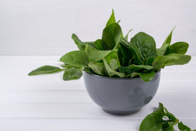 新鲜的在碗的庭院有机菠菜在土气背景准备好沙拉 库存图片
