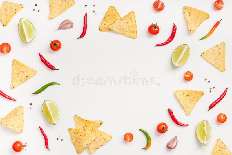 新鲜的墨西哥美食食品成分创造性的顶视图平的位置用玉米粉薄烙饼烤干酪辣味玉米片芯片大蒜胡椒在白色桌上的石灰蕃茄 免版税库存照片