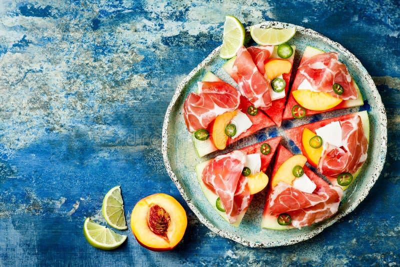新鲜的夏天西瓜薄饼用希腊白软干酪,桃子、熏火腿、墨西哥胡椒和蜂蜜在蓝色背景下毛毛雨 免版税库存图片