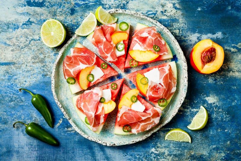 新鲜的夏天西瓜薄饼用希腊白软干酪,桃子、熏火腿、墨西哥胡椒和蜂蜜在蓝色背景下毛毛雨 图库摄影