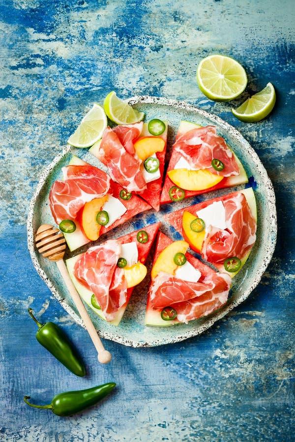 新鲜的夏天西瓜薄饼用希腊白软干酪,桃子、熏火腿、墨西哥胡椒和蜂蜜在蓝色背景下毛毛雨 免版税图库摄影