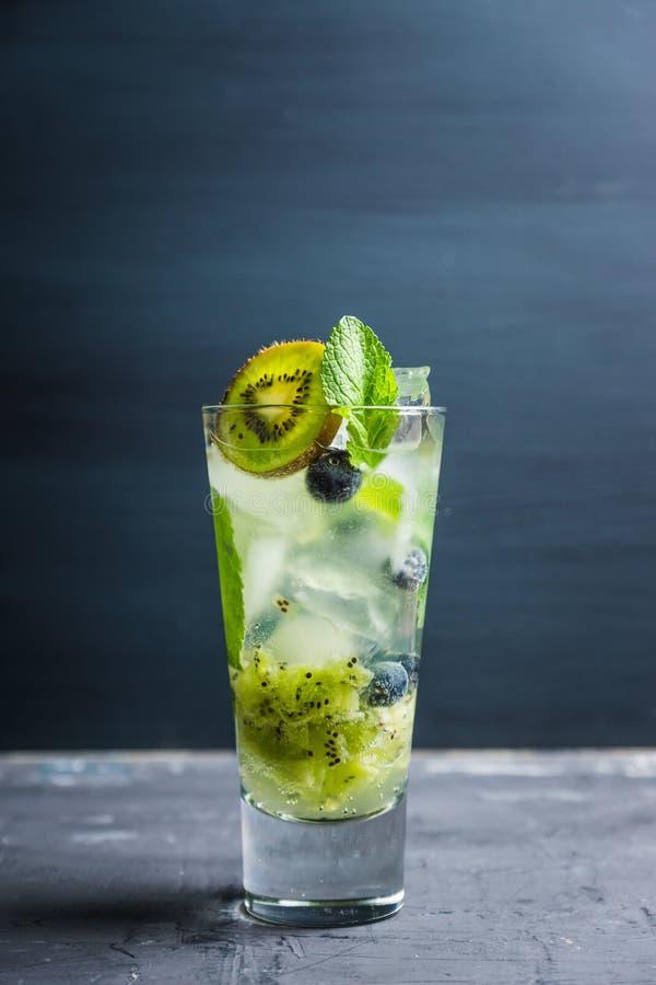 新鲜的夏天鸡尾酒用蓝莓和猕猴桃在木背景 免版税库存照片