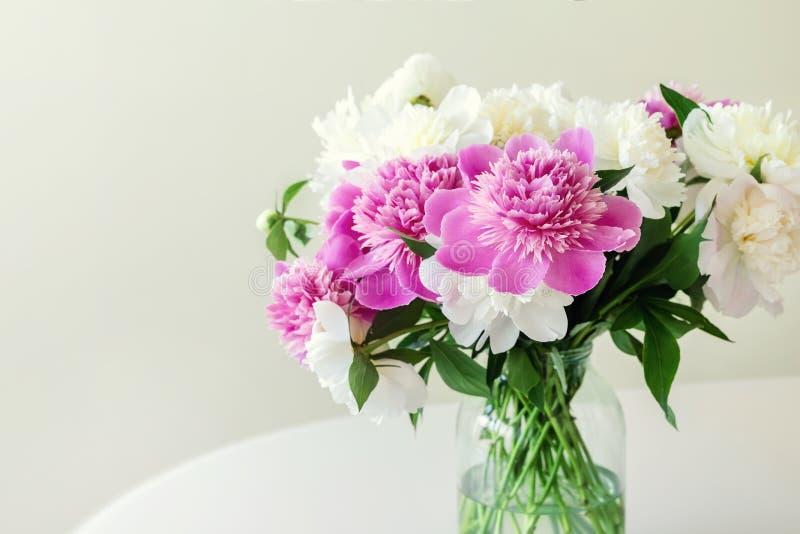 新鲜的大桃红色,白色和奶油色牡丹特写镜头花束在简单的玻璃瓶子的在室内扫视桌上 库存图片