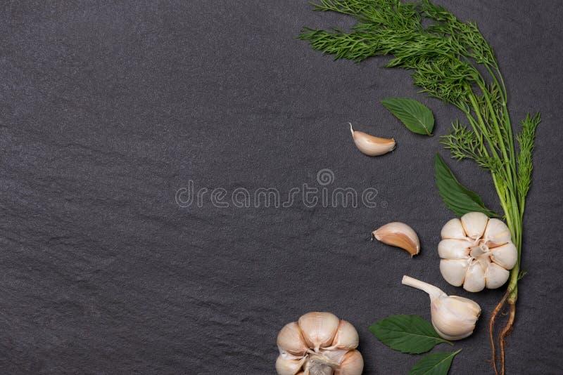 新鲜的大蒜 在黑石桌上的大蒜电灯泡 库存照片
