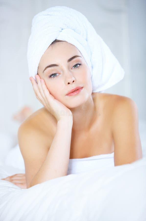 新鲜的妇女说谎的床用在面孔的手 库存图片