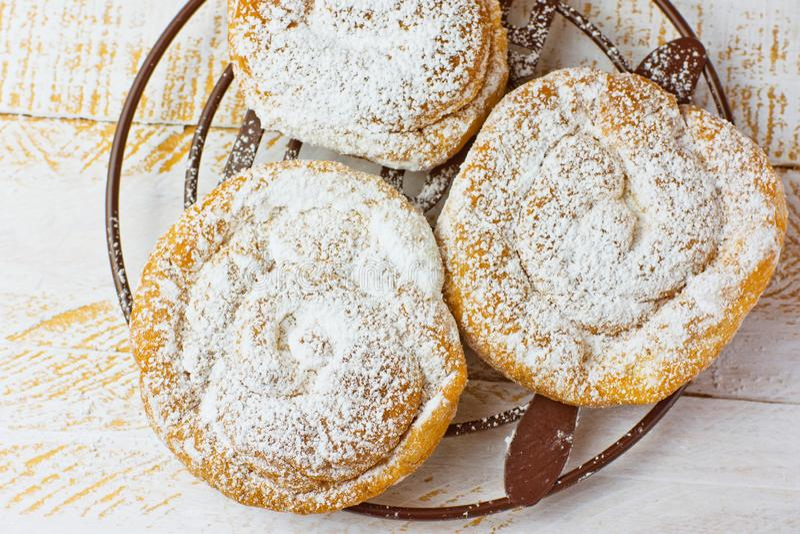 新鲜的家庭焙制的传统西班牙和菲律宾甜面包ensaimada拂去灰尘用在冷却的机架的糖粉在白色桌上 免版税库存照片