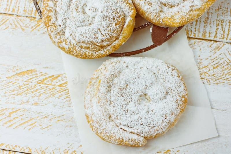 新鲜的家庭焙制的传统西班牙和菲律宾甜面包ensaimada洒与在冷却的机架的糖粉 免版税图库摄影