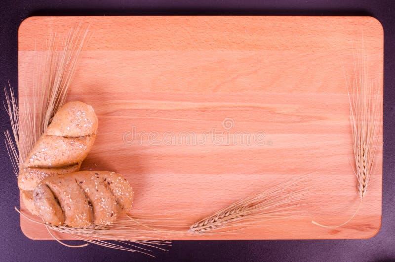 新鲜的小圆面包、曲奇饼和麦子耳朵在木背景中 库存照片