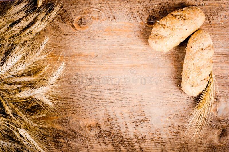 新鲜的小圆面包和麦子耳朵在木背景 框架 免版税库存照片