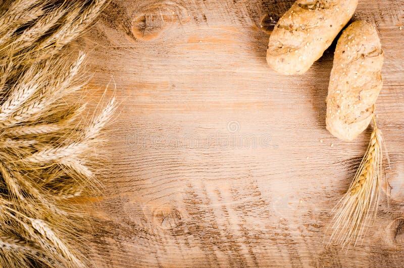 新鲜的小圆面包和麦子耳朵在木背景 框架 库存照片