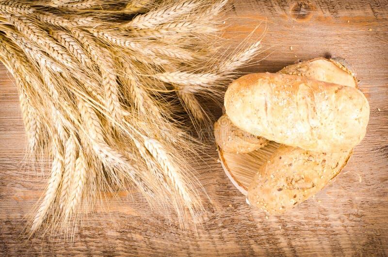 新鲜的小圆面包和麦子耳朵在黑背景中 免版税库存照片