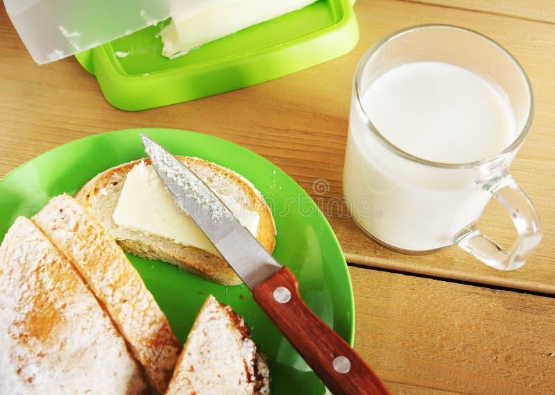 新鲜的小圆面包用黄油和一杯牛奶 免版税库存照片