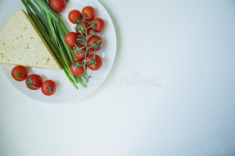 新鲜的干酪、分支新鲜的樱桃和绿色大蒜板材  o r 图库摄影