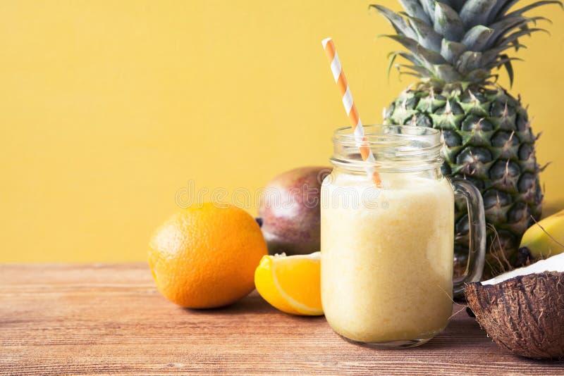 新鲜的异乎寻常的圆滑的人用果子和椰奶在黄色背景 库存图片