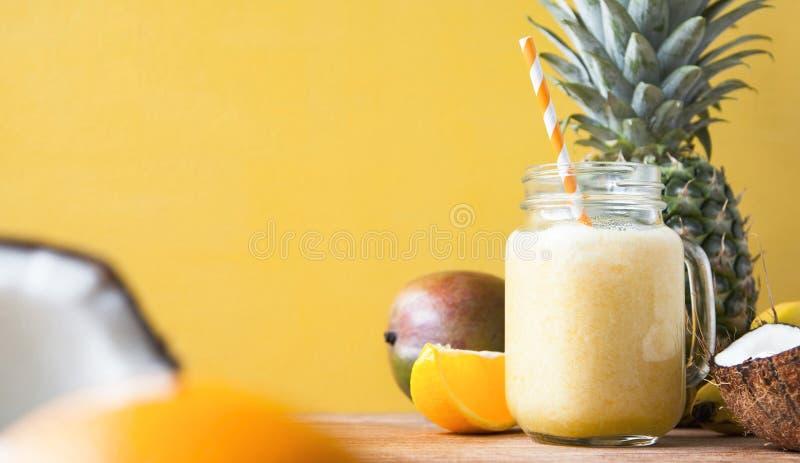 新鲜的异乎寻常的圆滑的人用果子和椰奶在黄色背景 免版税库存照片