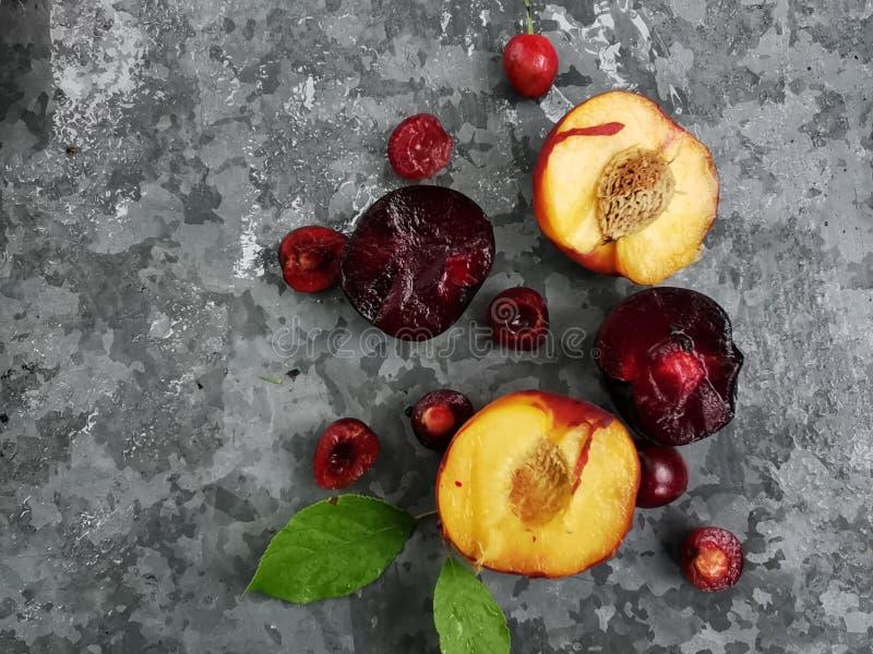 新鲜的成熟夏天莓果和果子、桃子、杏子、樱桃和李子在一块圆的板材在桌上 免版税库存照片