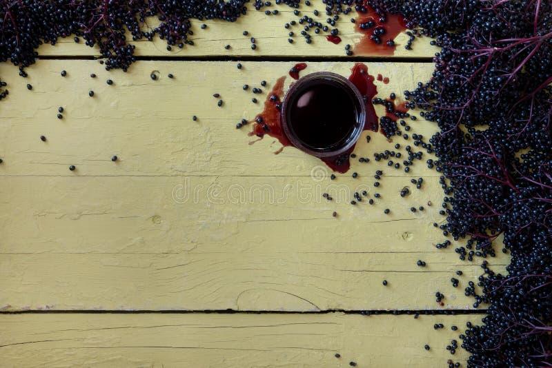 新鲜的成熟紫罗兰色黑接骨木浆果和接骨木浆果汁在土气灰色黄色桌上 免版税库存图片