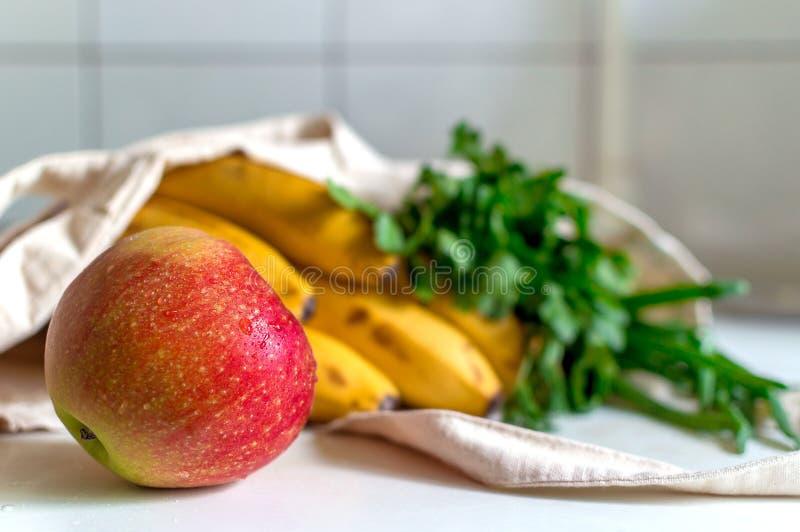 新鲜的成熟苹果、束荷兰芹和葱,香蕉和法国长方形宝石在帆布可再用的杂货大手提袋在厨房 免版税库存图片
